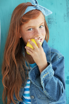 Cute redheaded child eating apple on vintage blue background